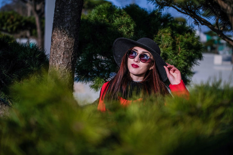 Hat Woman Adult Adults Only Beautiful Woman Day Lifestyles Long Hair Nature One Person One Woman Only Outdoors People Portrait Real People Sky Sunglass  Sunglasses Tree Tree Trunk Woman Portrait Women women around the world Young Adult Young Women