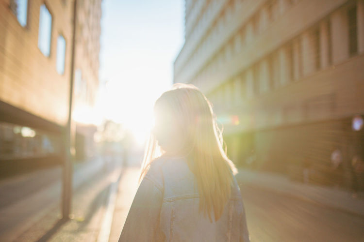 City One Person Architecture Lens Flare Sunlight Adult City Life Back Lit Headshot Standing Street Transportation Building Exterior Rear View Nature Women Young Adult Built Structure Casual Clothing City Street Hairstyle Outdoors Contemplation Springtime Decadence