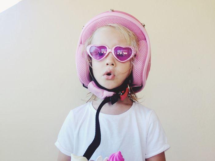 Portrait of cute girl in sunglasses wearing helmet against wall