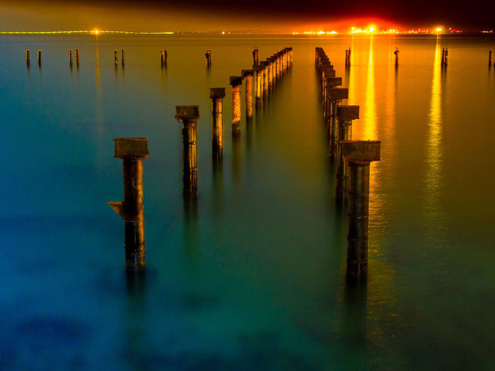 Wooden posts in lake against sky at sunset