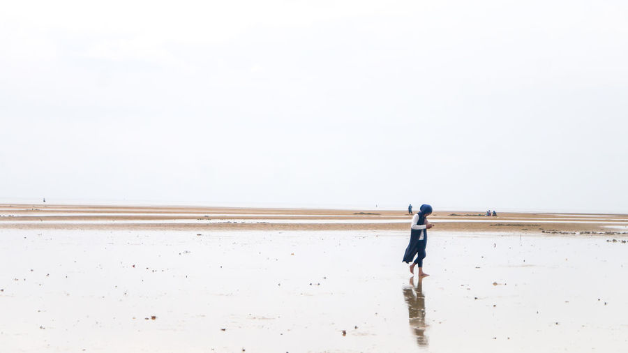 Rear view of man walking on beach against clear sky