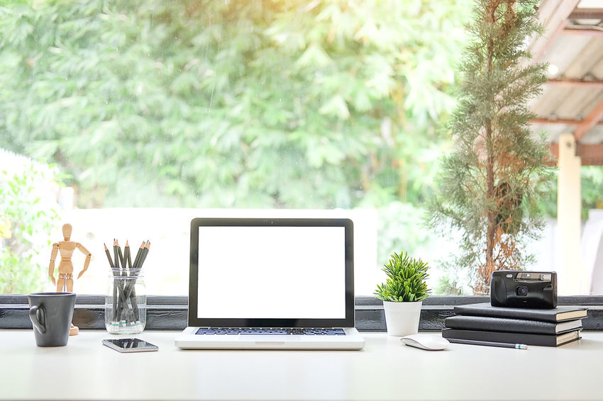 Office desk Work space stuff with notepad, laptop and coffee cup mouse notepad shot. Business Communication Computer Connection Crockery Cup Day Focus On Foreground Furniture Glass Glass - Material Indoors  Laptop Mug No People Plant Still Life Table Technology Tree Window Wireless Technology