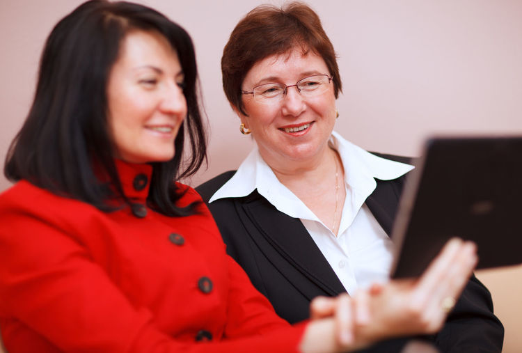 Amusement  Attractive Beautiful Business Businesswomen Caucasian Friendly Happiness Looking Person Portrait Real People Sitting Smiling Tablet Tablet Computer Two