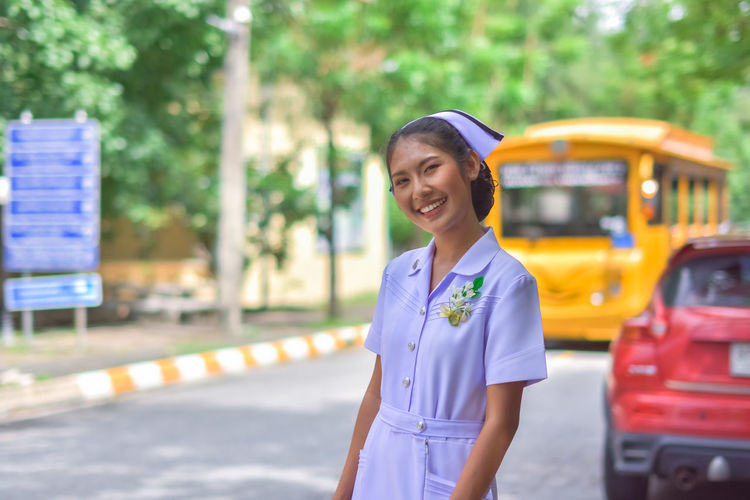 Smiling Young Nurse Standing On Road In City
