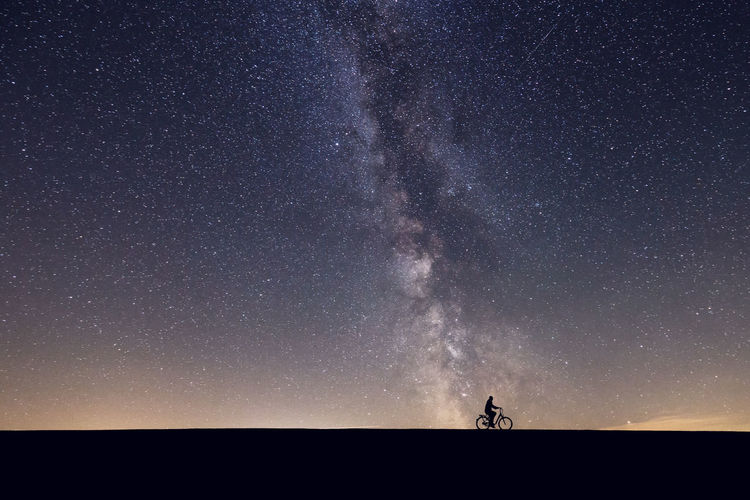 Silhouette man riding bicycle against star field at night