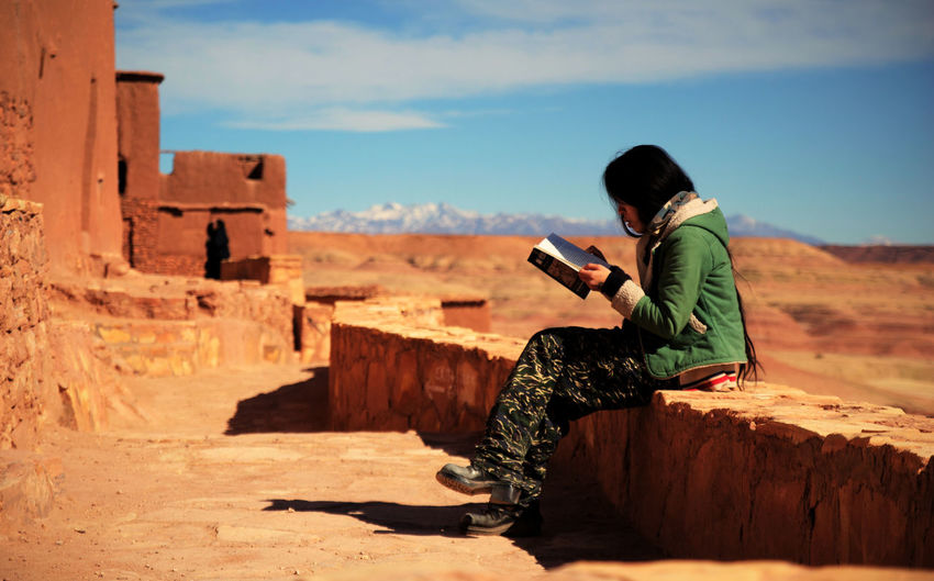 Side view of young woman reading book while sitting on retaining wall against sky