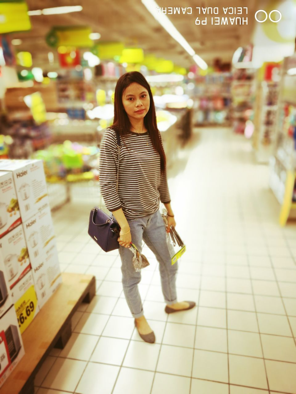 full length, one person, looking at camera, casual clothing, retail, real people, portrait, walking, smiling, store, focus on foreground, lifestyles, consumerism, market, young adult, indoors, standing, happiness, illuminated, day, young women, supermarket, people