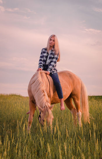 Portrait of teenage girl riding horse on land against sky