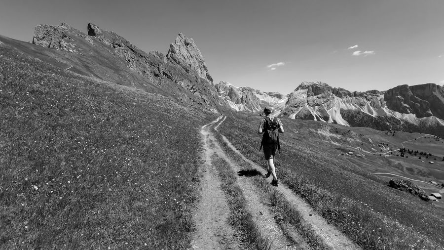 Man on a hiking path in the dolomites italy, seceda
