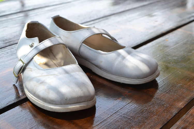 Close-up of white color shoes on table