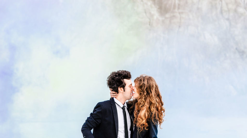 Cute stylish couple embrace and kiss against colorful smoke. Portrait of stylish young man in suit with tie and young woman with red hair. Concept of fashion wedding photography Stylish Suit Wedding Adult Couple - Relationship Emotion Hairstyle Heterosexual Couple Lifestyles Love Outdoors Real People Standing Togetherness Two People Women Young Men Young Women