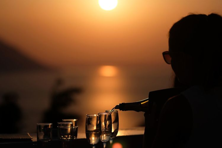 Silhouette man drinking glass against sea during sunset