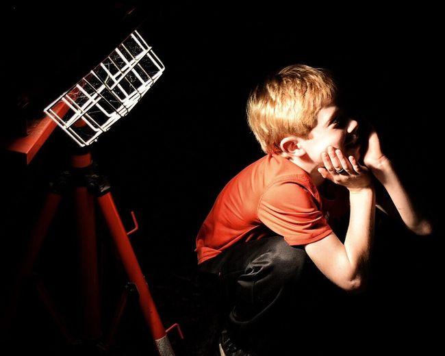 Boy Crouching By Illuminated Light On Tripod Against Black Background