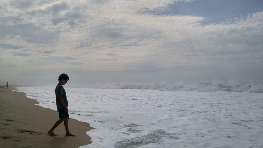 Full length of boy walking on sea shore at beach against sky