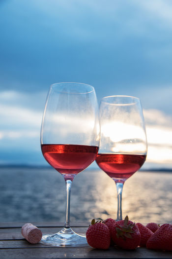 Close-up of red wineglasses by strawberry fruits and cork on table against sky