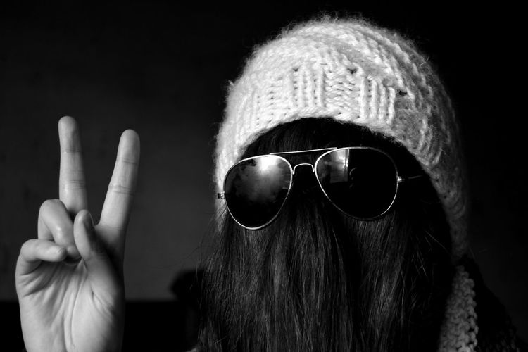 Woman with hair on face wearing sunglasses and knit hat while showing peace sign