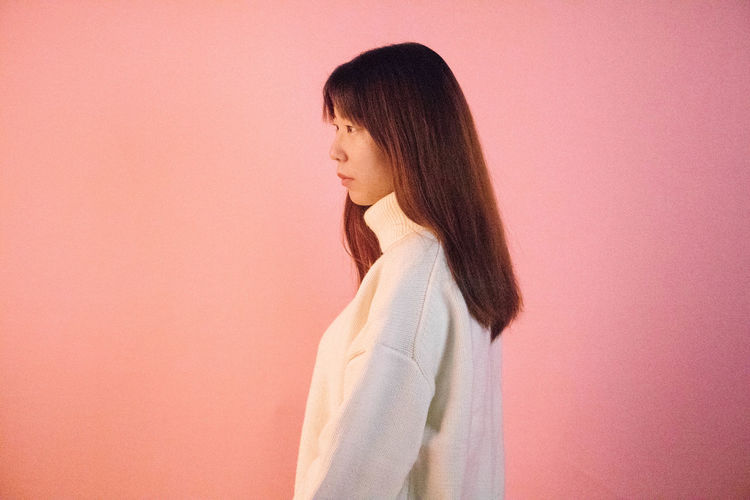 Side view of young woman standing against pink background