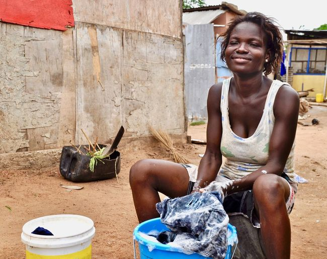 Smiling woman washing clothes in village
