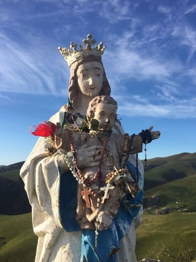 Virgin mary and jesus christ statue on field against sky
