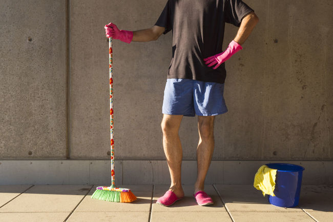 A house husband in pink fluffy slippers using colorful cleaning utilities Cleaning Cleaning Equipment Equal Rights  Household Hygiene Service Slippers Standing Adult Blue Broom Bucket Colorful Emancipation Gloves Human Body Part Human Leg Job Lifestyles Low Section One Man Only One Person Pink Color Shorts Wall - Building Feature