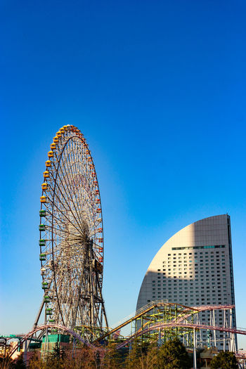 Cosmo landmark Ferris wheel park Amusement Park Ride Amusement Park Ferris Wheel Arts Culture And Entertainment Clear Sky Built Structure Sky Blue Architecture Carnival Traveling Carnival Nature Copy Space Day No People Outdoors Travel Destinations Building Exterior Low Angle View Sunny Yokohama Japan Ferris Wheel Funpark Architecture