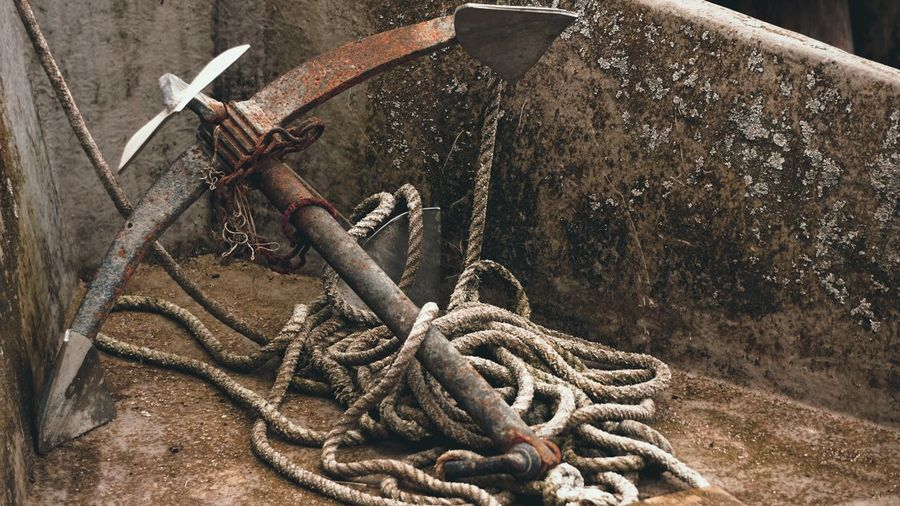 Close-up of rope tied on rusty metal chain