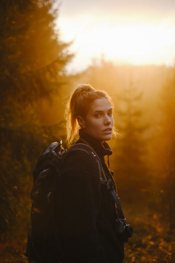 Portrait of woman standing in forest during sunset