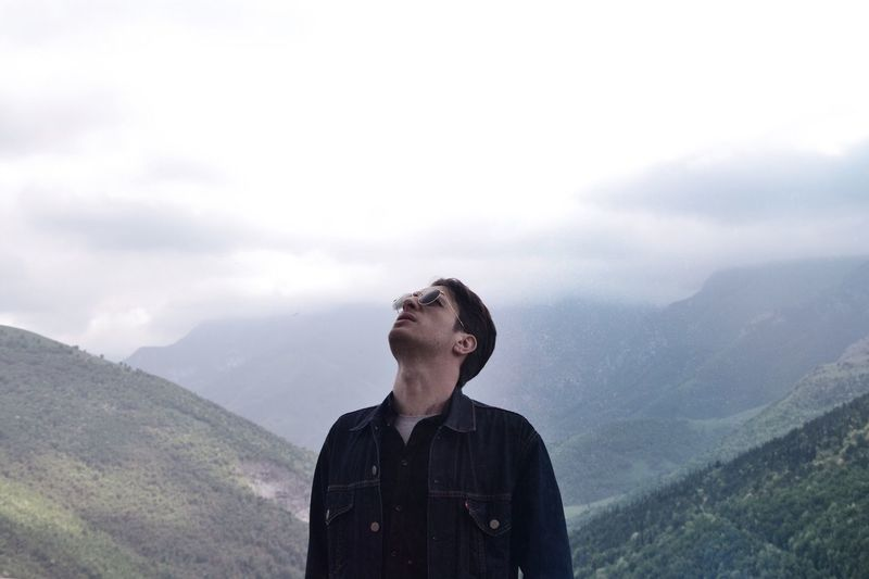Man in sunglasses standing against mountains during foggy weather