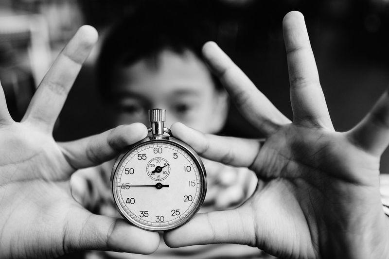 Close-up of boy holding stopwatch