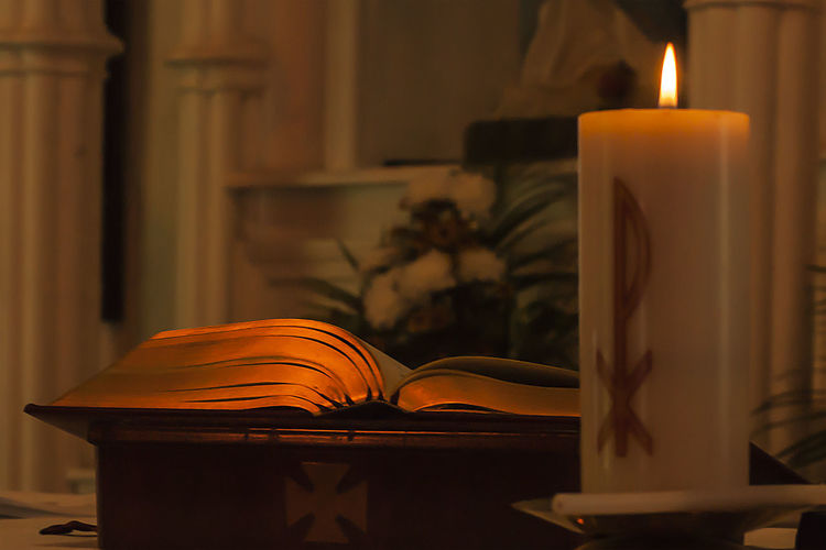 Close-Up Of Lit Candle And Bible On Altar