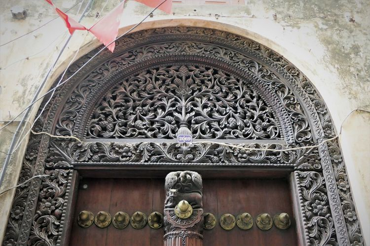 Stone Town Arabic Artwork Architecture Building Exterior Built Structure Day Human Representation Low Angle View Main Entrance No People Outdoors Sculpture Spirituality Wooden Door