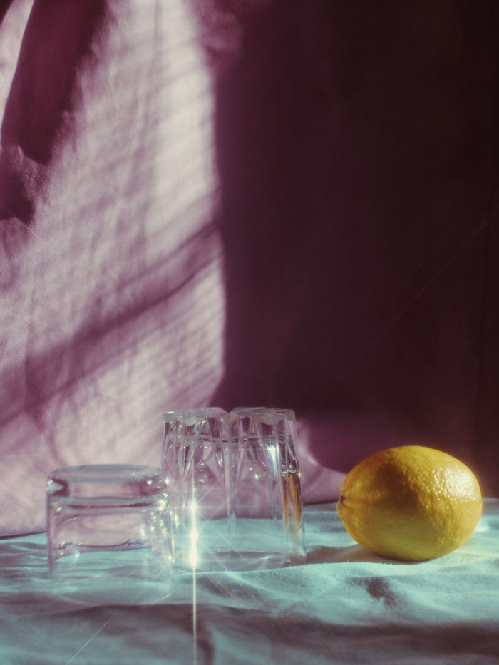 Close-up of glasses and lemon on tablecloth