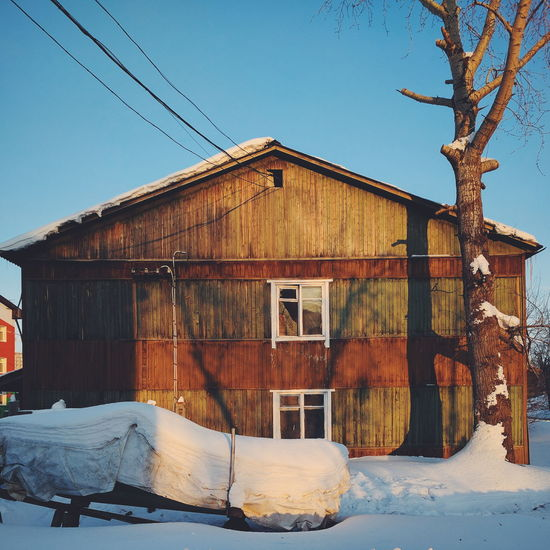 WOODEN HOUSE AGAINST CLEAR SKY DURING WINTER