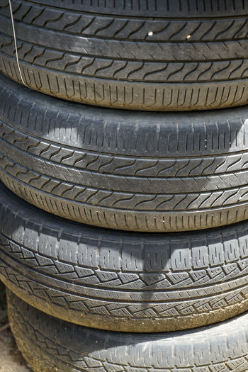 Stack of dusty old used car tyres showing groove lines under sunlight Automobile Transportation Wheel Abandoned Art And Craft Black Car Close-up Dump Dusty Focus On Foreground Full Frame Garage Groove Man :) Old Pattern Rubber Stack Still Life Textured  Tire Tyre Vehicle Wheel Wicker