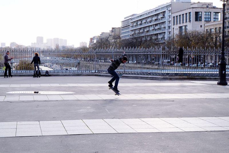 Man skateboarding on footpath in city