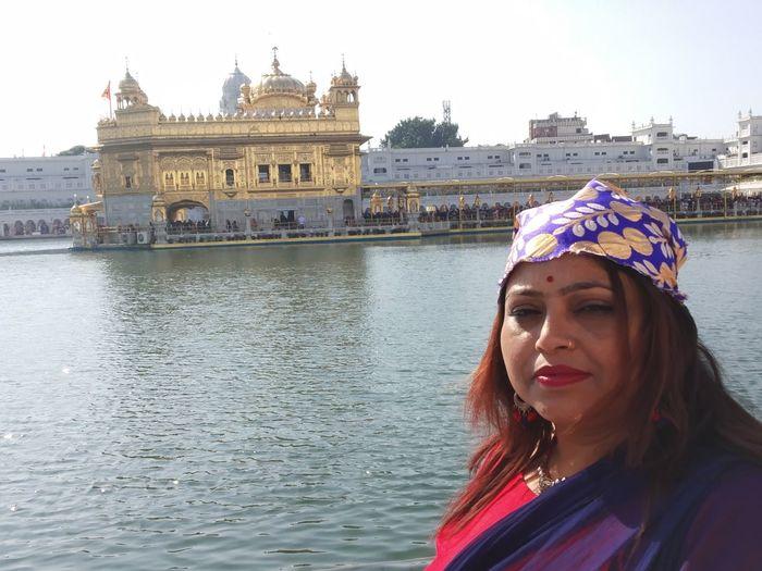 Portrait of woman standing against golden temple