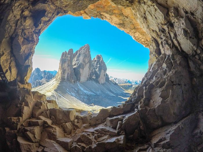 Rock formations seen through cave against sky