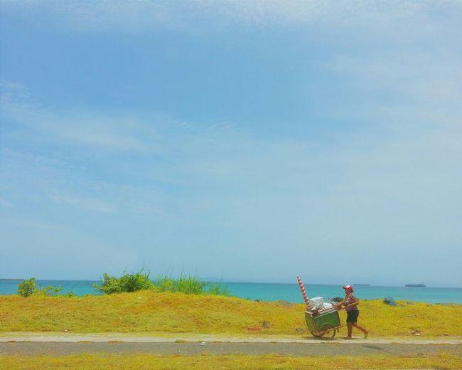People working on beach against sky