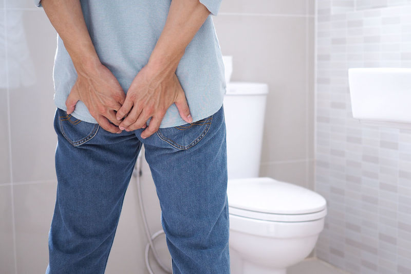 Midsection of man touching buttocks in bathroom