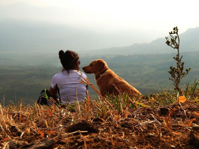 Rear view of woman with dog at mountain against sky