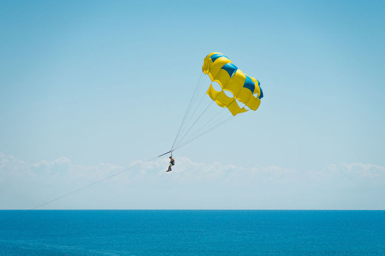 Parasailing over sea against sky