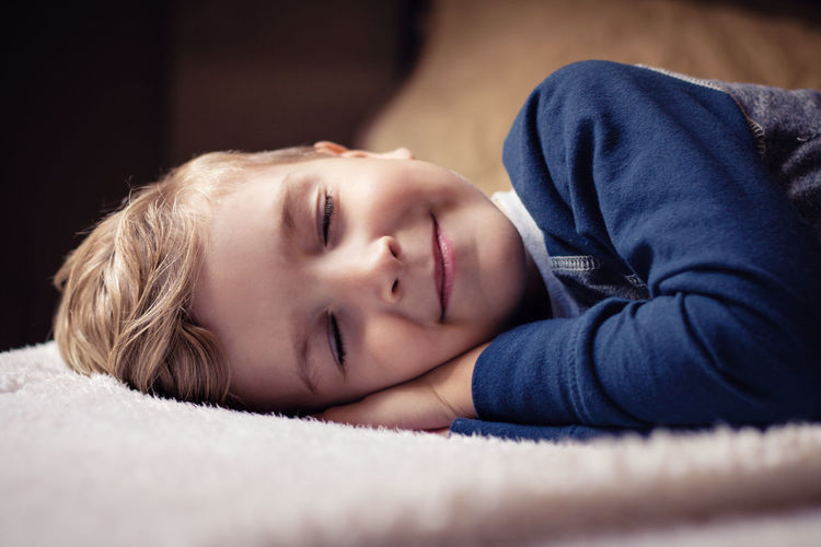 Close-up portrait of boy sleeping on bed at home