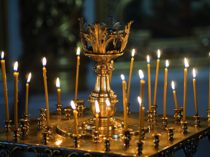 Close-up of lit candles on altar
