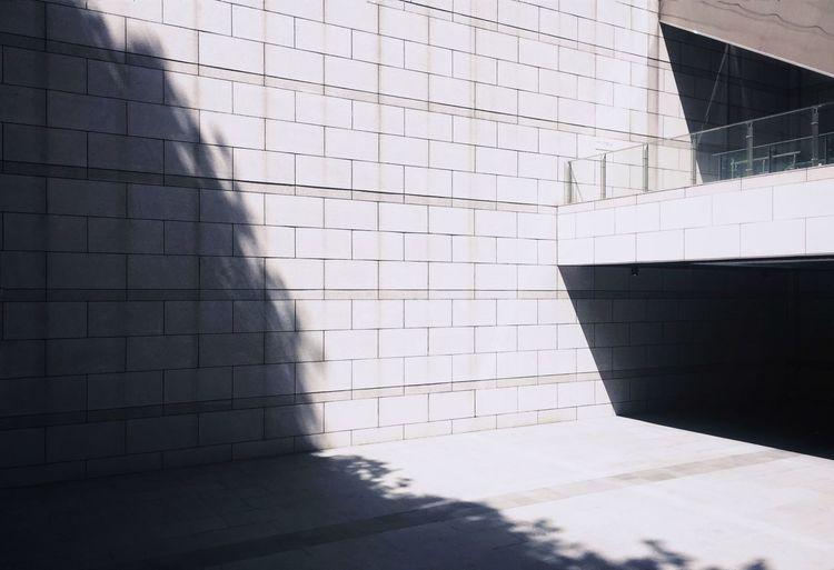 Sunlight falling on wall at sidewalk