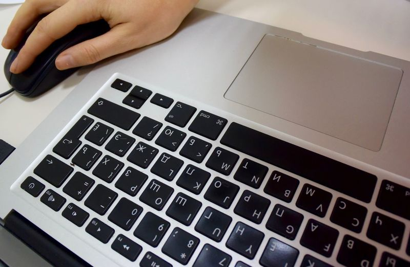 Cropped Image Of Hand Working On Laptop In Office