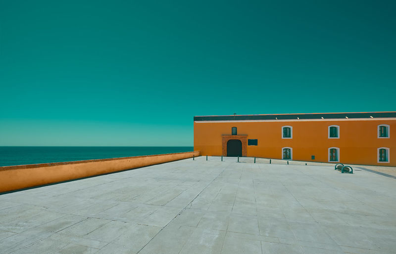 Empty esplanade with an orange building and sea in the background