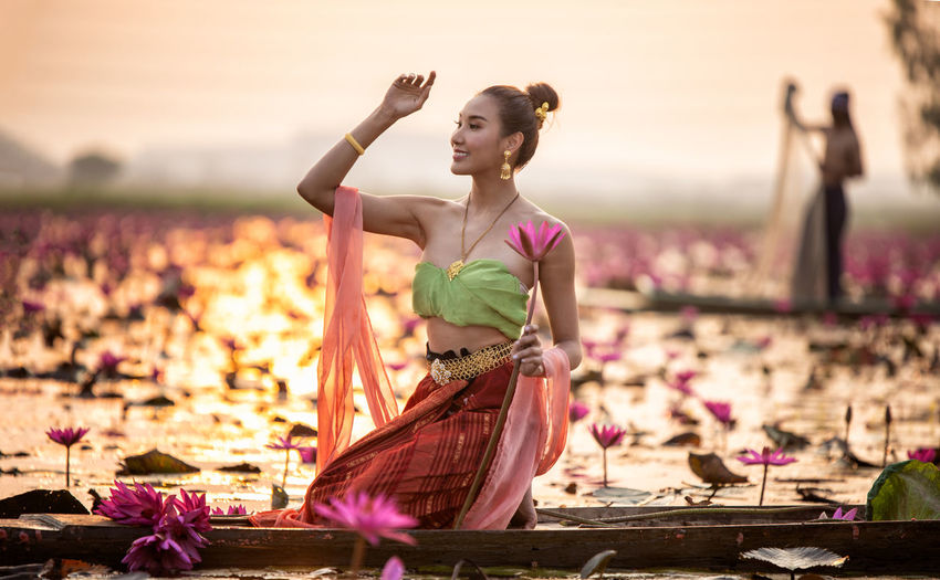 Young woman holding water lily in boat on lake during sunset