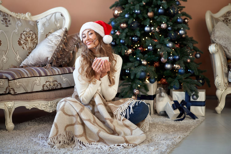 Full length of woman sitting by christmas tree at home