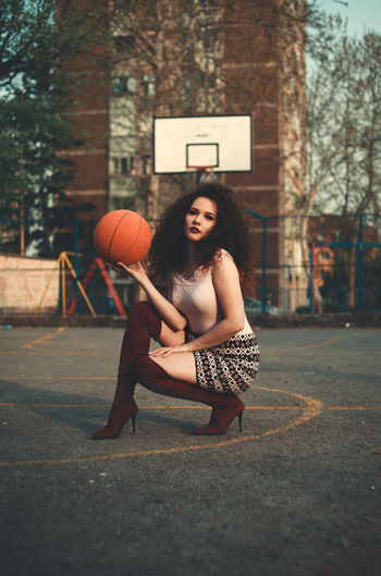 Portrait of beautiful young woman holding basketball on court