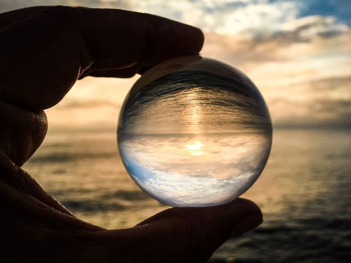 Close-up of hand holding crystal ball against sea at sunset